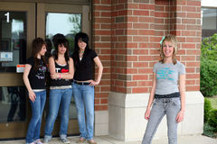 Mean Girls. Confident pretty blonde teen with clique of girls in the background Stock Images