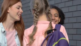 Mean girls stopping classmate in backyard, showing authority, provoking conflict. Stock footage stock video footage