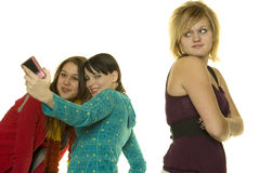 Mean Girls Take photos with cellphone. Two girls take photos with cell phone while leaving out a third girl Royalty Free Stock Photography