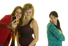 Mean Girls Take photos with cellphone. Two girls take photos with cell phone while leaving out a third girl Royalty Free Stock Image