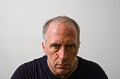 Mean man. Beautifully detailed real portrait of dangerous looking adult white man staring intensely at the viewer seemingly with hatred in eyes Royalty Free Stock Photos