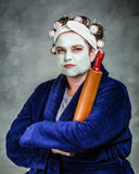 Mean and ugly housewife. With facial mask, hair rollers and rolling pin Stock Images