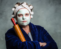 Mean and ugly housewife. With facial mask, hair rollers and rolling pin Royalty Free Stock Photo