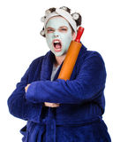 Mean and ugly housewife. With facial mask, hair rollers and rolling pin isolated on white Stock Photography