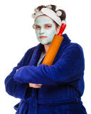Mean and ugly housewife. With facial mask, hair rollers and rolling pin isolated on white Stock Photos