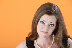Mean Woman. Mean-looking Caucasian woman in dress on orange background royalty free stock image