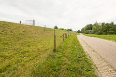 Meandering country road along an embankment with a fence Stock Photo