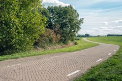 Meandering country road in a Dutch landscape. The road is paved with concrete paving stones in herringbone pattern. Beside the road trees are on one side and a stock images