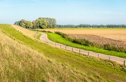 Meandering country road between an embankment and agricultural f. Ields. The photo was taken on a sunny day with a blue sky at the end of the Dutch summer season stock image
