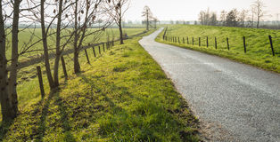 Meandering country road next to a dike Stock Photo