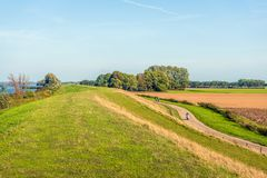 Meandering Dutch next to the wide river Hollands Diep. Meandering Dutch next to a wide river, a curved country road and colorful fields. Some unidentified people royalty free stock image