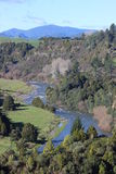 Meandering river in New Zealand. Meandering river in beautiful countryside of New Zealand lined by forrest and hills stock photo