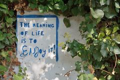 The meaning of life is to Enjoy it. Message on a wall Royalty Free Stock Photos