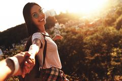 She means everything to him. Happy young woman looking at camera and smiling while holding hands with her boyfriend outdoors royalty free stock images