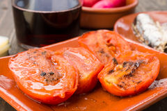 Means grilled tomatoes with olive oil, on  wood. Means grilled tomatoes with olive oil, on rustic wood Royalty Free Stock Photos
