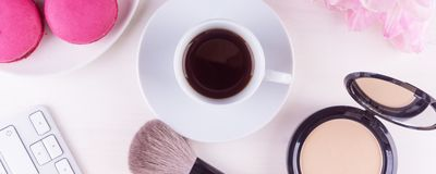 Panoramic mocap with a cup of coffee, Cake, powder and lipstick, female morning background. Means for a morning make-up - a panoramic mocap with a cup of coffee stock images