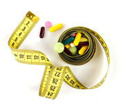 Means for weight lose. Drugs in colorful pills and capsules and yellow measure tape on white background, top view stock photo