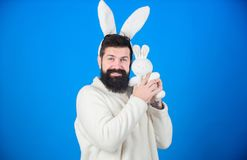 Meant for hugging. Happy hipster with long rabbit ears holding bunny toy. Fertility and new life. Bearded man in easter. Rabbit costume with hare toy. Easter stock photos