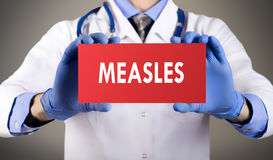 Measles. Doctor`s hands in blue gloves shows the word measles. Medical concept stock photos