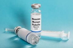 Measles Mumps Rubella Vaccine Vials With Syringe. Over Turquoise Background stock image