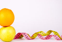 Measuer tape with friuts. Measure tape with orange and yellow apple Stock Image