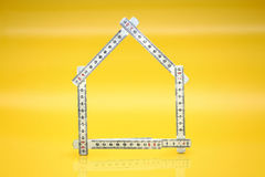 Measure. A meter and a yellow background as a symbol for a house Royalty Free Stock Images