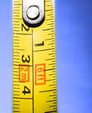 Measure. Yellow measure blurred on blue background Stock Photos