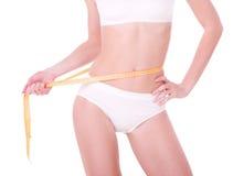 Measure on beautiful woman body. Yellow measure on beautiful woman body on white background Royalty Free Stock Photo
