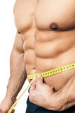 Measure body. An image of a handsome young muscular sports man measure Stock Photos