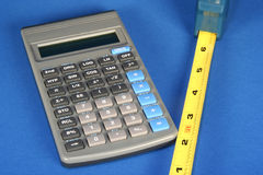 Measure and Calculate. Calculator and measuring tape on a blue background Stock Images