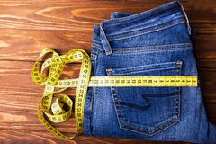Measure line tape roll on blue denim. Royalty Free Stock Images