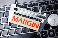 Measure margin of profit concept with caliper tool on computer keyboard Royalty Free Stock Image