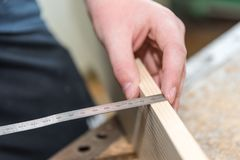 Measure with measuring tape wood - close-up. Joiner misses with tape measure thickness of wooden board - closeup carpenter workplace stock image