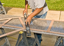 Measure of new granite countertops. A contractor measures and levels out a new granite kitchen countertop Royalty Free Stock Photography