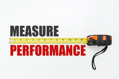 Measure performance. Measuring tape over the words measure and performance on white background Stock Photos