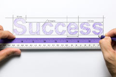 Measure success concept. Hand holding ruler and pencil measuring the word success Royalty Free Stock Images