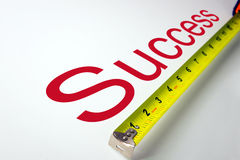 Measure success. Measuring tape over the word success on white background Stock Photos