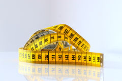 Measure tape. Yellow measure tape on white background Stock Photos