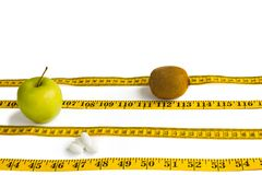 Measure tape, apple, peels and kiwi isolated on white royalty free stock photography