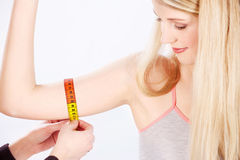 Measure tape around arm Stock Photo