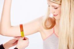 Measure tape around arm Stock Photo