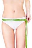 Measure tape around slim woman's hip Stock Image