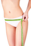 Measure tape around slim woman's hip Stock Photo