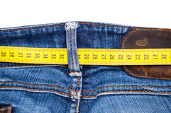 Measure tape and blue jeans Royalty Free Stock Images
