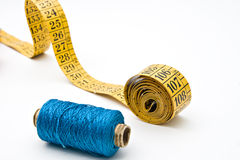 Measure tape and blue thread bobbin Royalty Free Stock Images