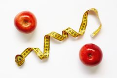 Measure tape and fresh fruits apples on white background. Loss weight, slim body, healthy diet concept royalty free stock photography