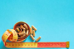 Measure tape with medicaments pills on light blue background. With copy space royalty free stock photos