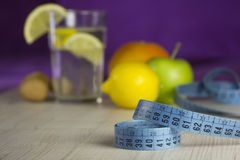 Measure tape and products for diet - weight loss program. Blue measure tape and products (fresh vegetarian fruits and healthy drink) for diet and weight loss Stock Photo
