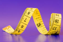 Measure tape on purple background Stock Photo