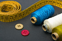 Measure tape, thread bobbins and buttons. Measure tape, a couple of thread bobbins and buttons Royalty Free Stock Image